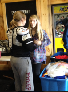 Erin helps a girl get a proper fitting set of shoulder pads :)